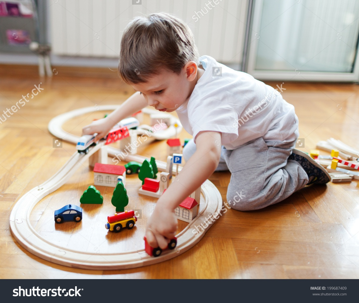 stock-photo-little-boy-playing-with-wooden-train-set-199687409