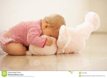 baby-girl-cuddling-pink-teddy-bear-home-26104834