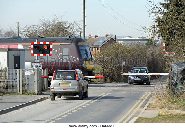 an-express-train-passing-through-a-half-barrier-level-crossing-whilst-d4m3at
