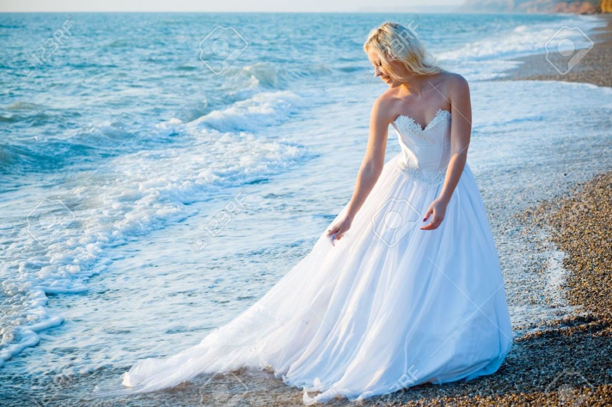 3081537-bride-in-white-wedding-dress-entering-sea-water-at-beach-stock-photo